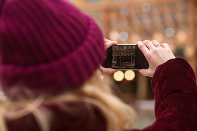 街の明るい背景の携帯電話で写真を撮る暖かい服装の女性