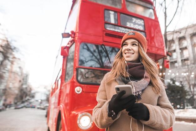 暖かい服を着た女性と彼女の手でスマートフォンはヘッドフォンで音楽を聴くし、観光赤いバスの背景に横に見える