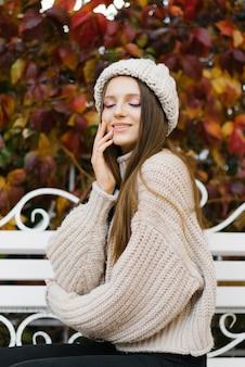 暖かい服を着た女性が秋の公園のベンチに座って天気を楽しんでいます