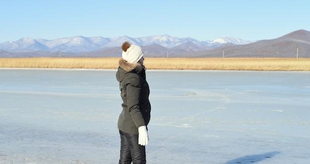 Женщина в теплой одежде стоит на льду и смотрит в сторону