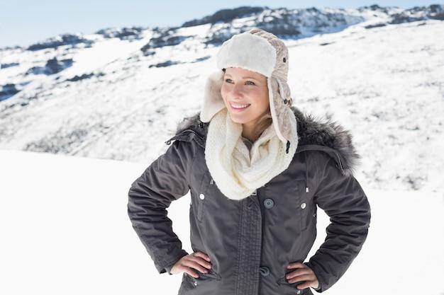 Женщина в теплой одежде, глядя в сторону на фоне снега