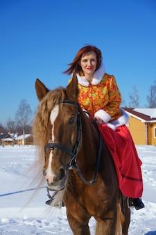 暖かいジャケットの女性は冬の季節に馬に乗る
