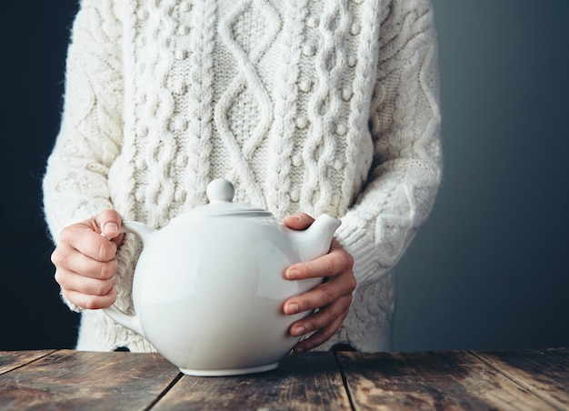 Женщина в теплом вязаном толстом свитере держит большой белый чайник с чаем на деревянном столе гранж. вид спереди, анфас, без лица.