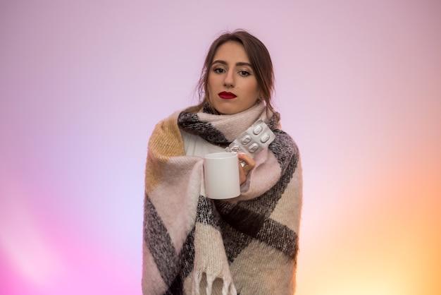 水ぶくれに丸薬を保持し、咳をしている暖かいスカーフの女性。病気の概念