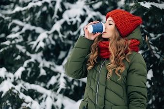 暖かい冬の服の女性は、冬の雪の日に屋外でコーヒーを飲みます。