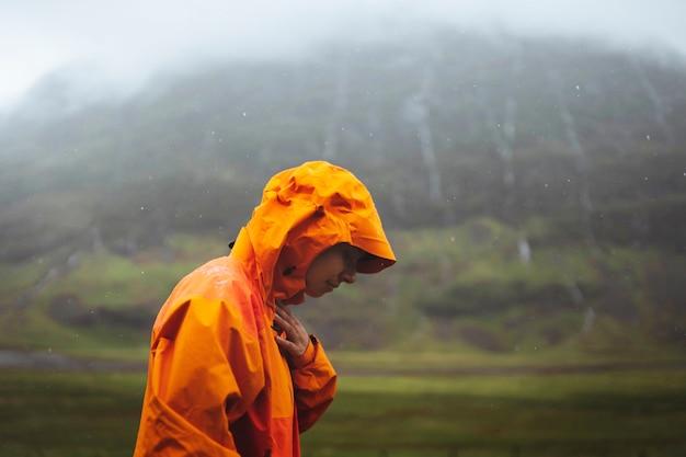 고지대에서 트레킹하는 동안 방수 재킷을 입은 여성