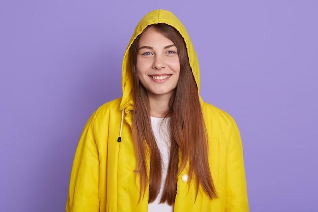 パーカーとジャケットを着て、魅力的な歯を見せる笑顔でカメラを直接見て、ポジティブを表現し、幸せを感じ、薄紫色の背景の上に孤立して立っている女性。