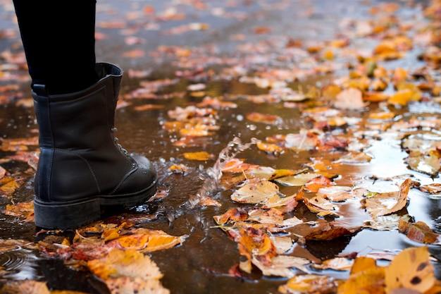 Женщина в погодных запечатанных сапогах идет по улицам осенью