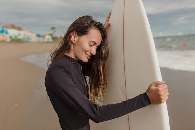 서핑을 준비하는 서핑 보드와 잠수복에 여자 햇빛에 눈을 감고 웃는 예쁜 여자