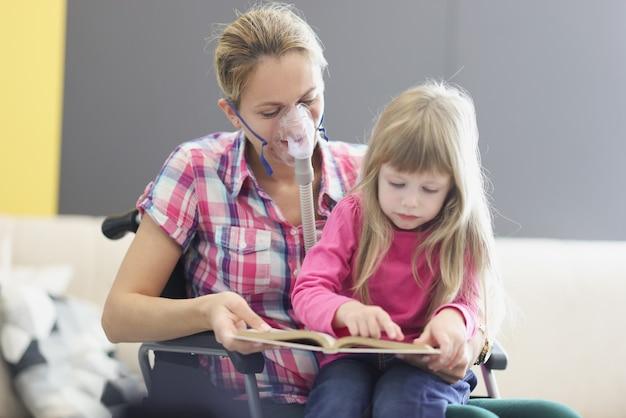 車椅子と酸素マスクの女性は小さな女の子と本を読んでいます