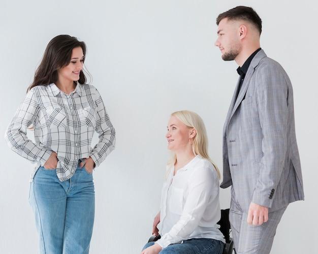 車椅子の同僚と会話する女性