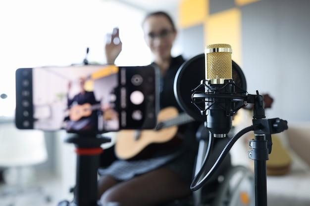 車椅子の女性がオンラインギターレッスンリモート音楽学習の概念を録音しています