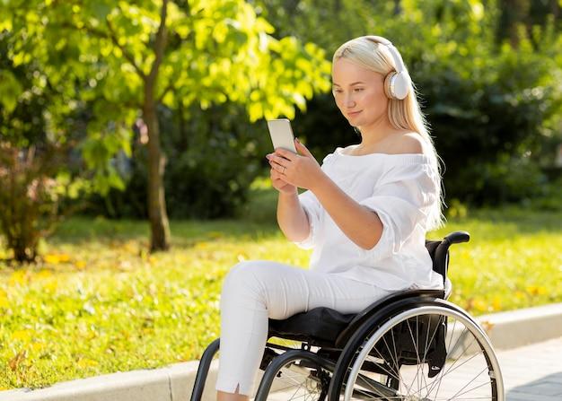 Женщина в инвалидной коляске, слушать музыку на открытом воздухе с мобильным телефоном