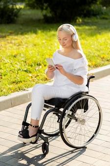 Женщина в инвалидной коляске слушает музыку на открытом воздухе со смартфоном