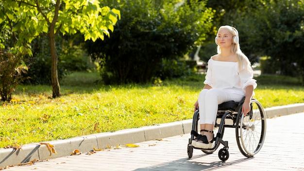 屋外で音楽を聴いている車椅子の女性