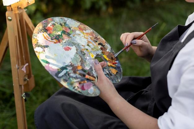 キャンバス上の自然絵画で屋外車椅子の女性