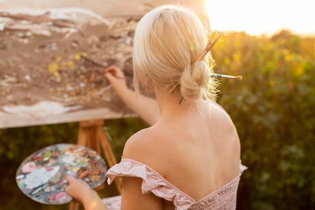 屋外で車椅子の絵を描く女性