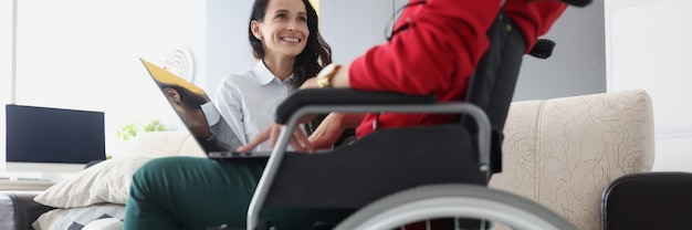 Женщина в инвалидной коляске с ноутбуком общается с другом