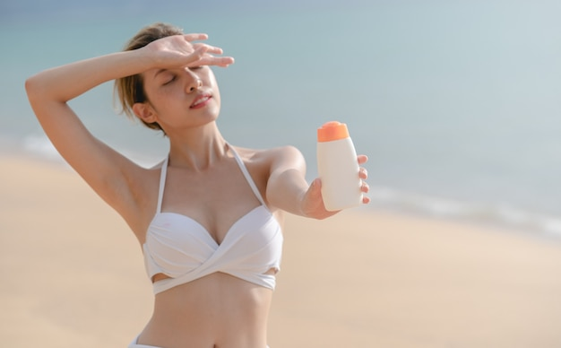 ビーチで日焼け止めのボトルを手に持っている白いビキニの女性。