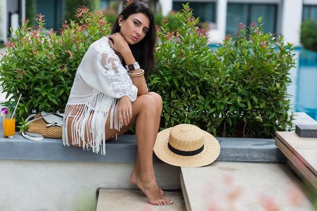 Женщина в белом бикини позирует в современном отеле в таиланде, одетая в стильную пляжную одежду в стиле бохо