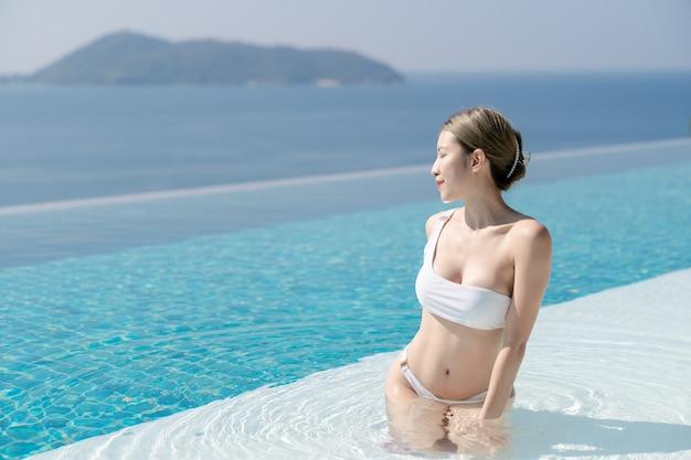 푸른 바다를 볼 수있는 인피니티 풀의 가장자리에서 편안한 흰색 비키니 입은 여자.