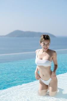 Женщина в белом бикини расслабляется на краю пейзажного бассейна с видом на синее море.