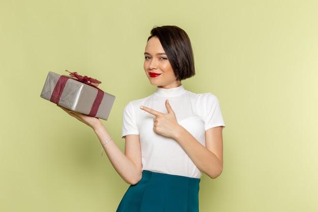 Женщина в белой блузке и зеленой юбке держит подарочную коробку