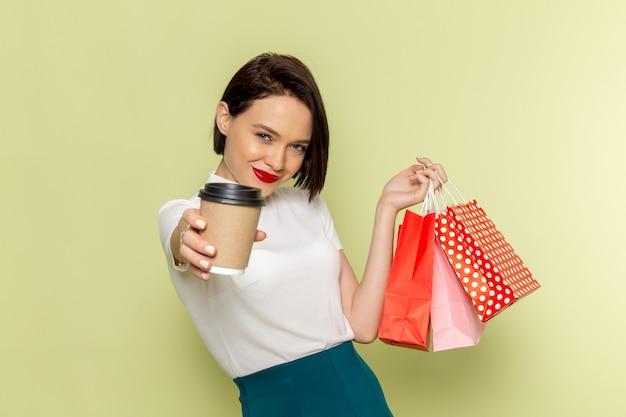 Женщина в белой блузке и зеленой юбке держит пакеты с покупками и чашку кофе