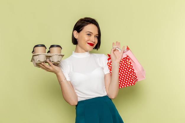 ショッピングパッケージとコーヒーカップを保持している白いブラウスと緑のスカートの女性