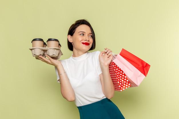 Женщина в белой блузке и зеленой юбке держит пакеты с покупками и кофейные чашки
