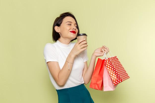 Женщина в белой блузке и зеленой юбке держит пакеты с покупками и кофе