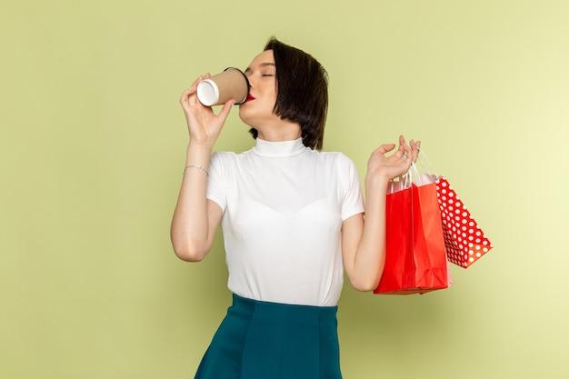 Женщина в белой блузке и зеленой юбке держит пакеты с покупками и пьет кофе