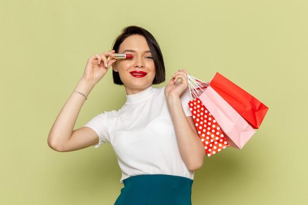 Женщина в белой блузке и зеленой юбке держит пакеты с покупками и помаду
