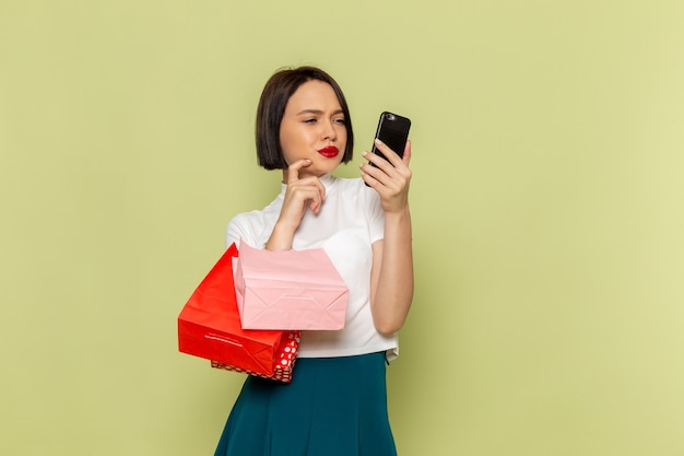 ショッピングパッケージと電話を保持している白いブラウスと緑のスカートの女性