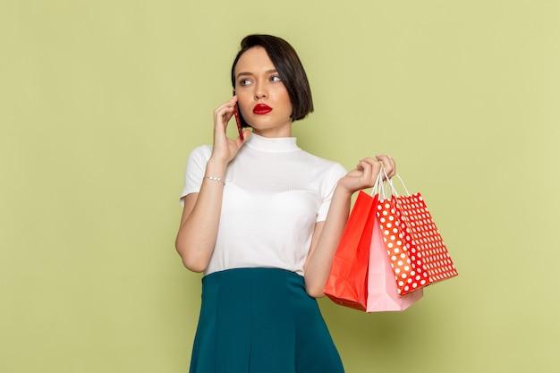 ショッピングパッケージを押しながら電話で話している白いブラウスと緑のスカートの女性