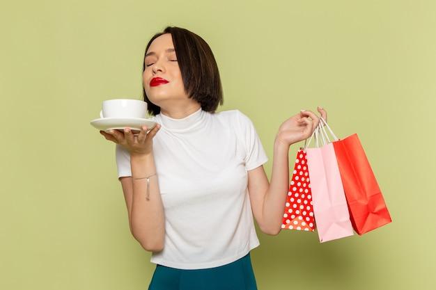 お茶のカップとショッピングパッケージを保持している白いブラウスと緑のスカートの女性