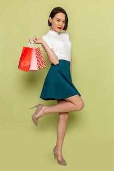 Женщина в белой блузке и зеленой юбке держит пакеты с покупками