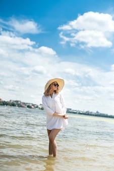 흰 블라우스와 더운 여름날에 쉬고있는 밀짚 모자에있는 여자가 호수를 걷고있다.
