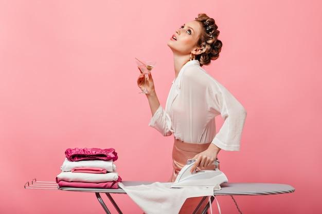 Женщина в белой блузке пьет мартини и гладит футболку на гладильной доске