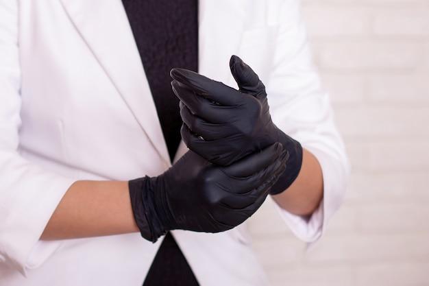Женщина в белом деловом костюме надевает черные перчатки