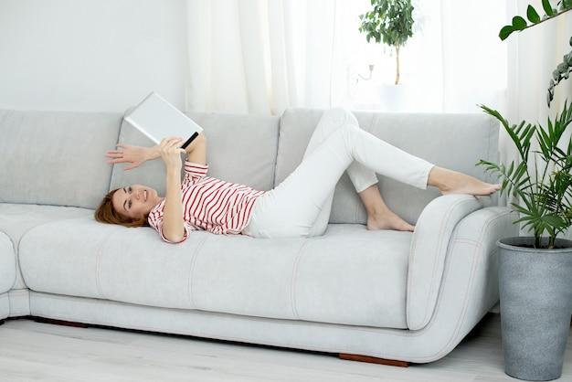 Женщина в белых одеждах общается по видеосвязи. общаться в чате и махать на экране компьютера.