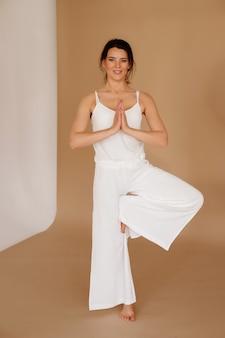 Vrikshasanaの白い服の女性ポーズスタジオでヨガをやっています。国際ヨガデー