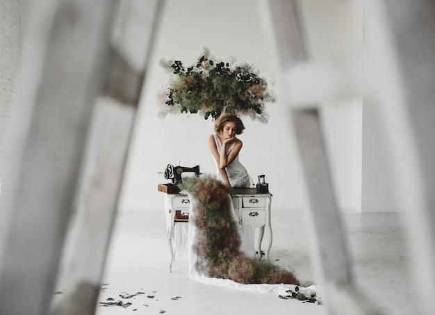 흰 옷을 입고 여자는 꽃과 재봉틀과 방에 앉아