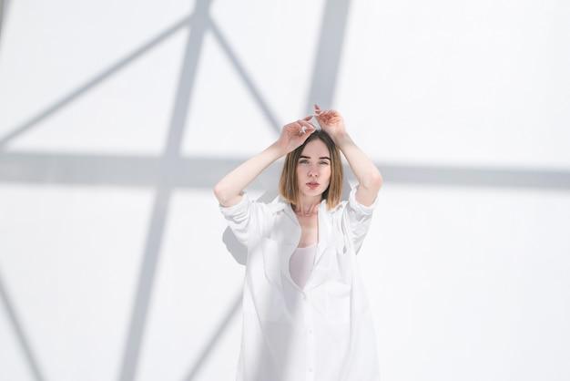 カメラで見ている白の抽象的な背景の上に立って白い服の女性