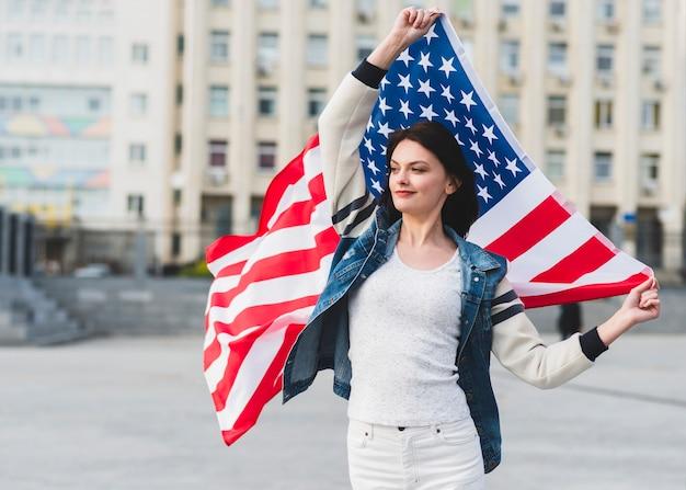 Женщина в белых одеждах с американским флагом на улице