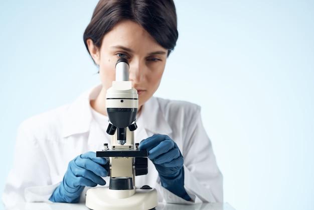 백의를 입은 여성 실험실 과학 현미경 분석