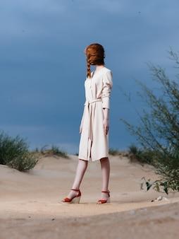 新鮮な空気のポーズをとってビーチの砂の上の白いコートの女性