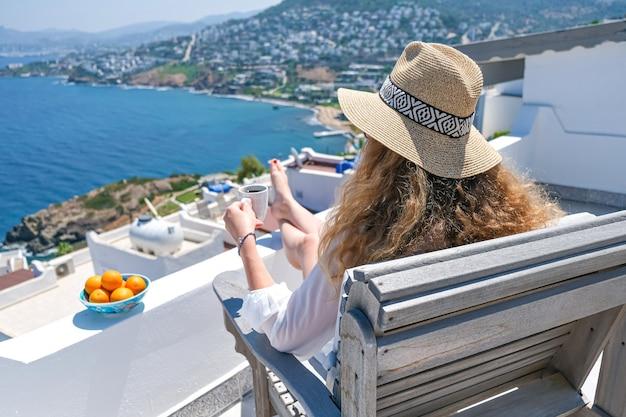 白いドレスと麦わら帽子と白いテラスのバルコニーのコーヒーカップの女性