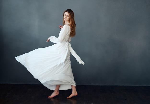 어두운 배경을 수행하는 흰 드레스 댄스 동작의 여자