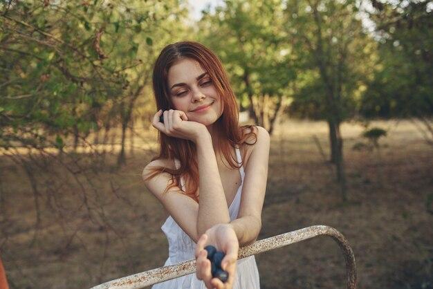 ブドウのクローズアップを食べる白いドレスの女性